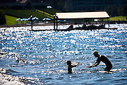 Marcos Donolo of Pullman reaches out to hold his daughter Kiara on Sanders Beach just before the Steve Omi Memorial Swim in Coeur d'Alene on Sunday morning.