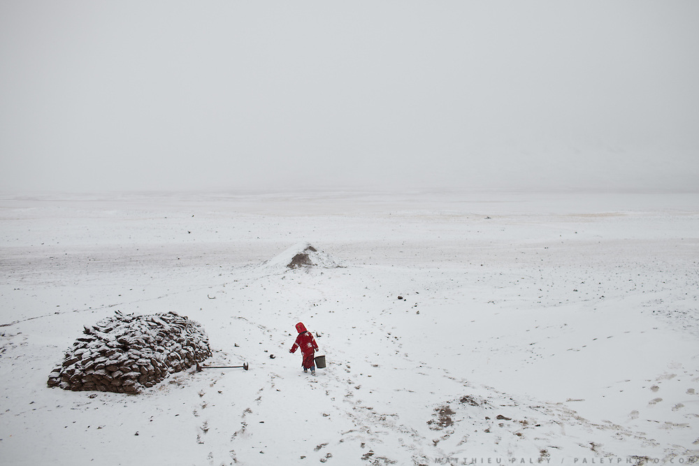A young girl rushed home to escape cold, camp of Ortobil, Manara (Sufi camp), near the borders with China and Tajikistan...Trekking with yak caravan through the Little Pamir where the Afghan Kyrgyz community live all year, on the borders of China, Tajikistan and Pakistan.