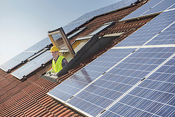 Engineer looking out of roof window to solar panels