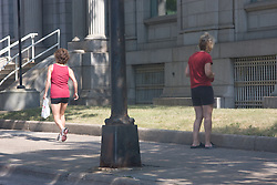 Two women who don't appear to know each other cross paths on a small section of sidewalk in Minneapolis, Minnesota
