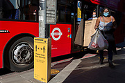 As the number of new Coronavirus cases in the UK climbs to 201,101, with UK deaths now standing at 30,076 - the highest recorded in Europe, passengers exit a bus next to a Transport For London (TFL) sign asking the public to maintain safe social distances while travelling on the capital's public transport during the continuing Covid lockdown, on 6th May 2020, in south London, England. Front doors on London buses are now disabled to avoid exposure of drivers to the virus, plus no fares are being taken on journeys to further avoid card reader contact.