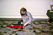 Young boy wearing pyjamas playing with red fire engine toy on Christmas morning, British culture 1967