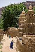 Faithful enters Endé mosque. Most Dogon Country mosques are in Sudanese style and built with mud. The Dogon Country is the most visited part of Mali with tourists visiting its tipical  villages that can be located on the cliff, on the sandy plain or in the rocky plateau