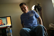"""BIRMINGHAM, AL – JUNE 13, 2015: Matthew Seals, 47, in his new home in the Winchester Hills neighborhood. <br /> <br /> In April 1998, a deadly F5 tornado ripped through the suburbs of Birmingham, Alabama, killing 32 people and destroying hundreds of homes. Seventeen years later, Matthew Seals is still learning to cope with the loss of his youngest son, who was killed in the storm. With help from Habitat for Humanity, Seals completed construction on a new home in 2015, where he continues to raise his remaining children and his new life as a paraplegic. Despite his own suffering from the tragedy, Seals volunteers with Habitat to help other families find their own form of stability through home ownership. """"Habitat gives you an opportunity to help yourself,"""" Seals said. """"Not just for the immediate need, but for the long term to become more self-sufficient, more self-confident, and more self-reliant."""""""