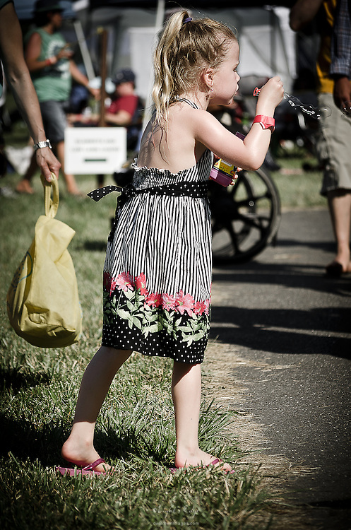 A youngster enjoys time with her bottle of bubbles at the 2013 Appel Farm Arts & Music Festival.