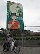 Color film photograph of a Vietnamese man sitting on his motorbike in front of a propaganda billboard asking people to clean vegetables before eating them to prevent against pesticide consumption, Hanoi, Vietnam, Southeast Asia