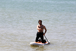 © Licensed to London News Pictures. 30/05/2021. Brighton, UK. A surfer in the sea on the hottest day of the year so far. According to the Met Office, a high of 24 degrees celsius is forecast for the bank holiday weekend, after weeks of rain in the South East of England. Photo credit: Dinendra Haria/LNP