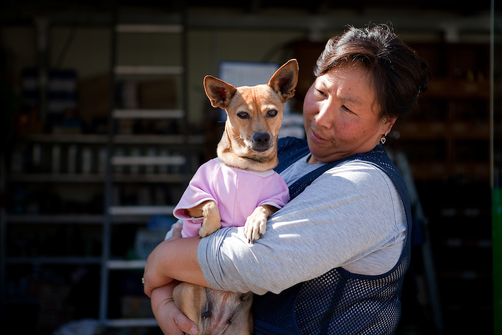 Portrait of a Korean woman holding her dog wearing a pink dress in front of a shop in Jukbeon, South Korea.