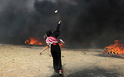April 13, 2018 - Khan Younis, Gaza Strip - A Palestinian woman hurls stones towards Israeli security forces during clashes in a tent city protest where Palestinians demand the right to return to their homeland, at the Israel-Gaza border, in Khan Younis in the southern Gaza Strip, April 13, 2018  (Credit Image: © Ashraf Amra/APA Images via ZUMA Wire)