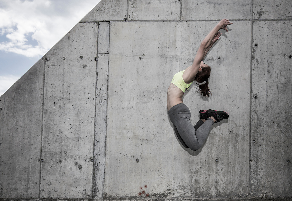 Woman jumping high ib front of weathered concrete wall