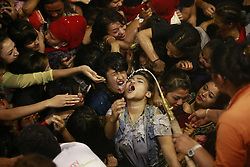 September 17, 2016 - Kathmandu, Nepal - Young Nepalese women drink local homemade alcohol from the mouth of idol Swet Bhairab on the fifth-day of the eight-day long Indrajatra festival, celebrated to honor Deity Indra, the King of Heaven and Lord of Rains at Basantapur Durbar Square in Kathmandu, Nepal on Saturday, September 17, 2016. Indrajatra is the biggest religious street festival held annually in Nepal. Singing, mask dance, rejoicing chariot processions and devotees offering prayers along with other rituals hold the eight-day festival celebrated by both Hindus and Buddhists. (Credit Image: © Skanda Gautam via ZUMA Wire)