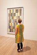 Woman wearing a brightly coloured and patterned dress looks at a piece by the weaving artist Annie Albers at a retrospective show of her work at Tate Modern art gallery on 13th October 2018 in London, United Kingdom.