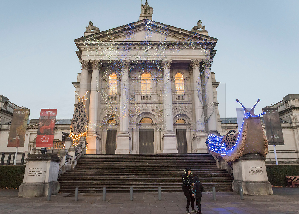 """© Licensed to London News Pictures. 30/11/2018. LONDON, UK.  The new Tate Britain Winter Commission, devised by the Turner Prize nominated artist Monster Chetwynd, is unveiled.  The artist, formerly known as """"Marvin Gaye"""" and """"Spartacus"""", has transformed Tate Britain's iconic Neo-Classical façade to mark the winter season with a new piece inspired by the winter solstice, involving a dazzling light display and elements of sculpture.  Winter Commission 2018: Monster Chetwynd will be switched on daily from 1st December 2018 - 28 February 2019.  Photo credit: Stephen Chung/LNP"""