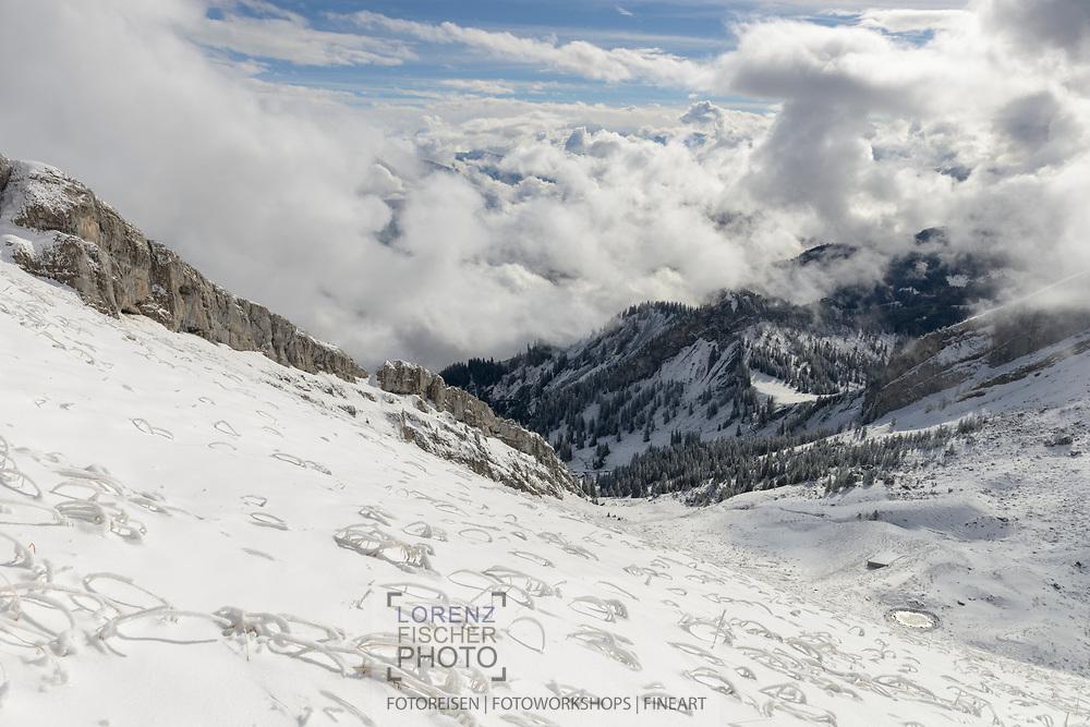 Ausblicke vom Pilatus über den Südgrat des Tomlishorns und Obwaldner Hügelketten in die Hochalpen nach dem ersten Wintereinbruch an einem wolkenverhangenen Tag im Oktober