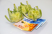 Cost of food concept Kohlrabi (German Turnip or turnip cabbage) with bank notes on white