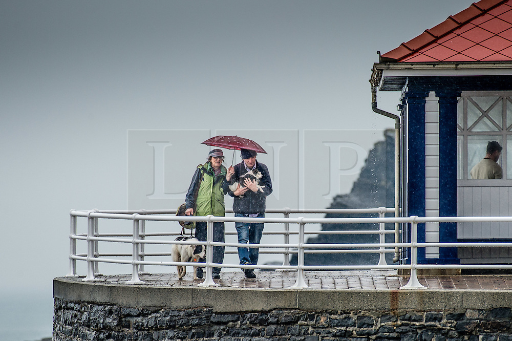 © London News Pictures. 07/05/2016. Aberystwyth, UK. People on  the damp promenade in Aberystwyth sheltering under their umbrellas. As much of England swelters on the hottest day of the year so far, much of the west and Wales is experiencing a wet and rainy day. A Met Office amber warning is in place for the whole of Wales for the rest of the day, with the possibility of torrential localised downpours. Photo credit: Keith Morris/LNP
