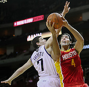 Jan 12, 2012; Houston, TX, USA; Houston Rockets power forward Luis Scola (4) shoots over Sacramento Kings point guard Jimmer Fredette (7) during the first quarter at the Toyota Center. The Rockets won 103-91. Mandatory Credit: Thomas Campbell