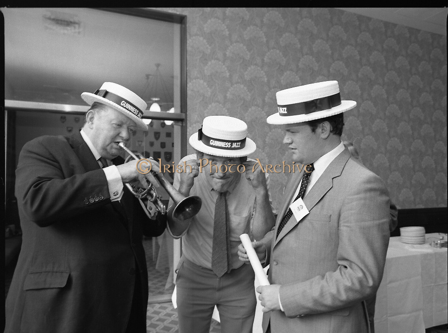"""Guinness Jazz Festival, Cork.01/07/1982.Topping the bill at the festival were,The First Lady of Jazz, """"Ella Fitzgerald"""",The legendary """"B.B.King"""" and the unique """"Modern Jazz Quartet""""..At the reception Mr Bobby Howick, Trade Director Guinness Group Sales, tries out the trumpet of Mr Pieter Sluis (centre) {but not very well}..Mr Sluis is a member of The Bruxelles Jazz Group,who played at the reception. Also pictured is Mr Jim Mountjoy, Metropole Hotel, Cork. Mr Mountjoy is a Co-festival Director."""