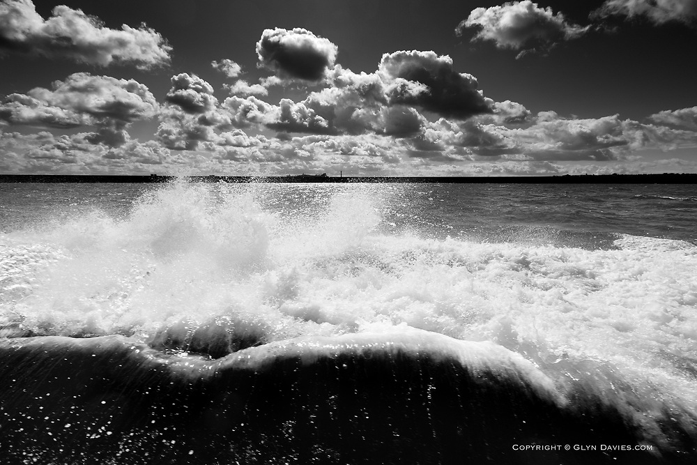 Huge wake from the twin engines of a powerful Severn Class lifeboat as it powers back into Holyhead Harbour from the South Stack lighthouse on Holy Island, Anglesey, in morning light with sunshine and fluffy white clouds and a calm sea.