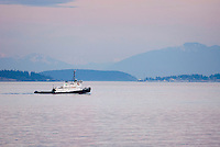 Tugboat making way through Rosario Strait in the San Juan Islands, Cascade Mountains in the distance, Washington USA