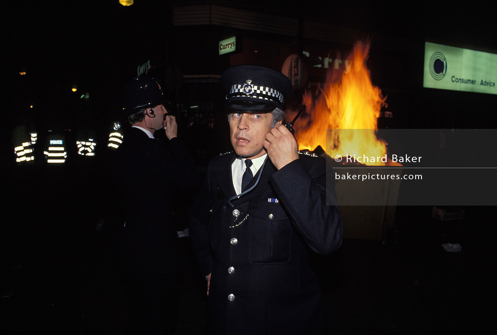 As the flames of a fire strted deliberately burns in the background, police officer listens to his radio during disturbances about the Poll Tax, the controversial property tax imposed by Margaret Thatcher's government and which ultimately brought about her downfall weeks later, on 20th October 1990, in London, England.