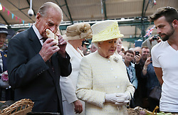 Queen Elizabeth II and the Duke of Edinburgh (left) talk with stall holder Simon Matthews during a walk around St. Georges Market in Belfast, on day two of their visit to Northern Ireland.
