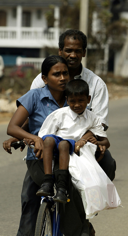 A family on a bicycle move through the tsunami-devastated area of Galles, south west coast of Sri Lanka, on January 13, 2005..Photo by Darrin Zammit Lupi