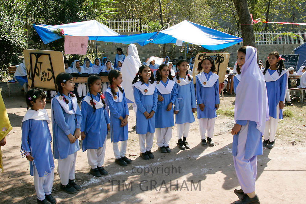Schoolchildren have lessons outdoors after earthquake in village of Pattika, Pakistan