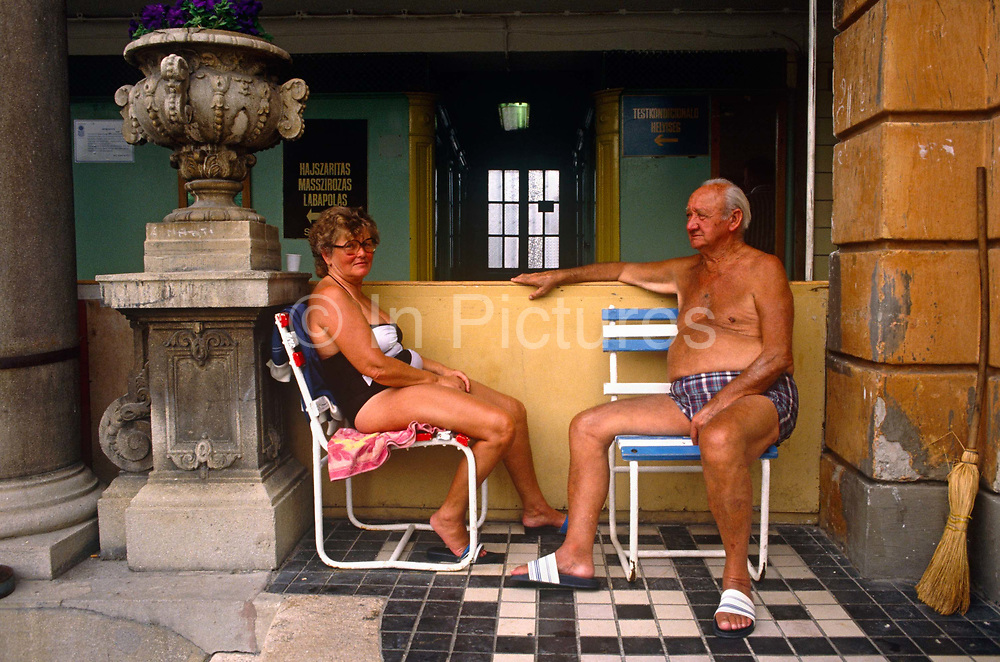 By a Neo-baroque ornamental pillar and vase, a Hungarian couple are seated on beach chairs, not at the seaside but in Budapest's famous Széchenyi thermal bath. Having bathed in thermal waters that are piped through this health resort in the middle of the capital city, the man and woman wear swimming costumes in the warm summer morning where hundreds flock to. Budapest is especially known for its spas just as Germany is. The Széchenyi Medicinal Bath  (Széchenyi-gyógyfürdő) is the largest medicinal bath in Europe. Its water is supplied by two thermal springs, their temperature is 74°C/165°F and 77°C/171°F, respectively. The bath can be found in the City Park, and was built in 1913 in Neo-baroque style to the design of Győző Czigler.