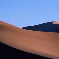 Namibia, Namib Nauklift National Park, Setting sun lights huge red sand dunes at Sossusvlei