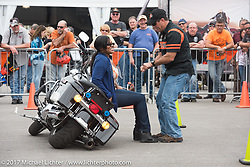 Rob Grimsley, a Harley-Davidson Regional Police Representative, explains how to pick up a bike with very little effort to Terra Green, New Orleans, LA at the Harley-Davidson Display during Daytona Bike Week. Daytona Beach, FL. USA. Monday March 13, 2017. Photography ©2017 Michael Lichter.