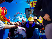 """02 JUNE 2017 - SAMUT SAKHON, THAILAND: Devotees of the City Pillar Shrine get off a boat after the parade on the Tha Chin River. The Chaopho Lak Mueang Procession (City Pillar Shrine Procession) is a religious festival that takes place in June in front of city hall in Samut Sakhon. The """"Chaopho Lak Mueang"""" is  placed on a fishing boat and taken across the Tha Chin River from Talat Maha Chai to Tha Chalom in the area of Wat Suwannaram and then paraded through the community before returning to the temple in Samut Sakhon. Samut Sakhon is always known by its historic name of Mahachai.      PHOTO BY JACK KURTZ"""