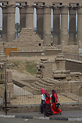 Young Egyptian women walk in front of the ancient Egyptian columns of Luxor Temple, Luxor, Nile Valley, Egypt. The temple behind was built by Amenhotep III, completed by Tutankhamun then added to by Rameses II. Towards the rear is a granite shrine dedicated to Alexander the Great and in another part, was a Roman encampment. The temple has been in almost continuous use as a place of worship right up to the present day.
