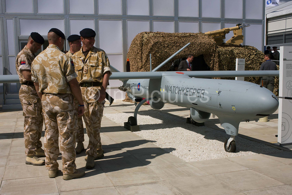 British Army soldiers gather outside the hospitality chalet of aerospace manufacturer Thales. Standing in mid-day sun, the troops are dressed in ISAF desert uniform, alongside a company-built Watchkkeper an unmanned aerial vehicle (UAV). Watchkeeper WK450 is a £800 million contract awarded in July 2005 to Thales to provide the British Army with  or all weather, Intelligence, Surveillance, Target Acquisition and Reconnaissance (ISTAR) use. It has a weight of 450 kg and a payload capacity of 150 kg, and will have a typical endurance of 17 hours.