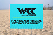 A masking and physical distancing sign at the WCC Beach Volleyball Championship at Dockweiler State Beach, Saturday, May 1, 2021, in Los Angeles.