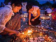 28 OCTOBER 2015 - YANGON, MYANMAR:     Women light oil lamps during observances of Thadingyut at Botataung Pagoda in Yangon. Botataung Pagoda was first built by the Mon, a Burmese ethnic minority, around the same time as was Shwedagon Pagoda, over 2500 years ago. The Thadingyut Festival, the Lighting Festival of Myanmar, is held on the full moon day of the Burmese Lunar month of Thadingyut. As a custom, it is held at the end of the Buddhist lent (Vassa). The Thadingyut festival is the celebration to welcome the Buddha's descent from heaven.     PHOTO BY JACK KURTZ