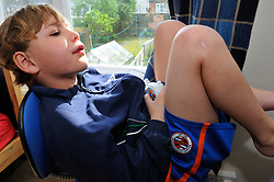 Bored 8 yr old in his bedroom holding xbox controller. MR