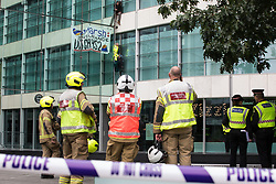 London Fire Brigade firefighters observe two climate activists from HS2 Rebellion who scaled the Tower Place West building in the City of London in protest against the involvement of insurance company Marsh in the HS2 high-speed rail project on 2nd September 2021 in London, United Kingdom. Marsh insure subcontractors working on HS2.