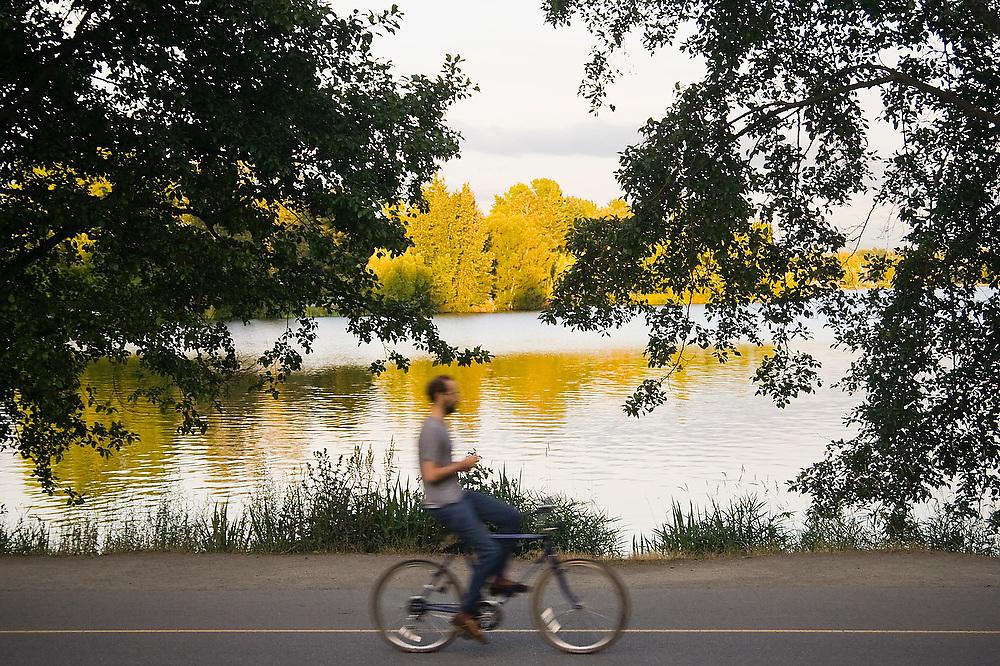 A man rides his bike around Green Lake, a popular city park in Seattle, Washington.