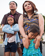 Cyana Nguyen, 4, is overwhelmed with community talk as her family looks on during a National Night Out event on Sark Court in Milpitas, California, on August 7, 2014. (Stan Olszewski/SOSKIphoto)