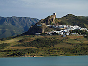 A view of Zahara -- one of Andalusia's famous pueblos blancos -- with Embalse de Zahara (a reservoir) in the foreground. The Sierra de Grazalema rise in the distance. Andalusia, Spain.