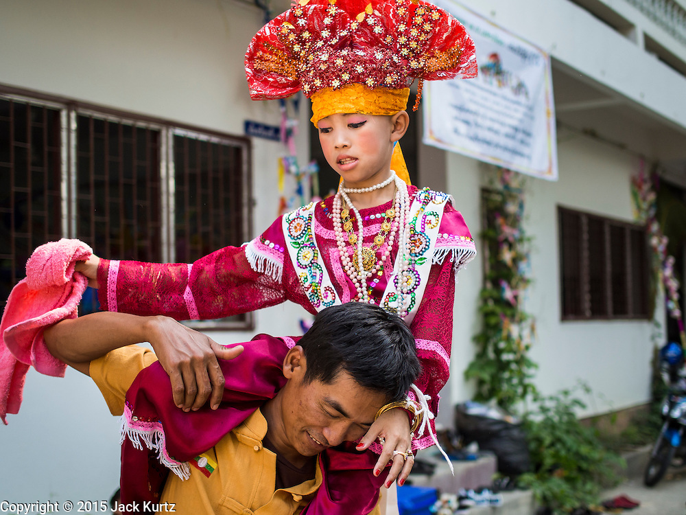 """04 APRIL 2015 - CHIANG MAI, CHIANG MAI, THAILAND:  A boy being ordained as a Buddhist novice dances during the Poi Sang Long Festival at Wat Pa Pao in Chiang Mai. The boys ride on men's shoulders during the festival because their feet aren't allowed to touch the ground. The Poi Sang Long Festival (also called Poy Sang Long) is an ordination ceremony for Tai (also and commonly called Shan, though they prefer Tai) boys in the Shan State of Myanmar (Burma) and in Shan communities in western Thailand. Most Tai boys go into the monastery as novice monks at some point between the ages of seven and fourteen. This year seven boys were ordained at the Poi Sang Long ceremony at Wat Pa Pao in Chiang Mai. Poy Song Long is Tai (Shan) for """"Festival of the Jewel (or Crystal) Sons.     PHOTO BY JACK KURTZ"""