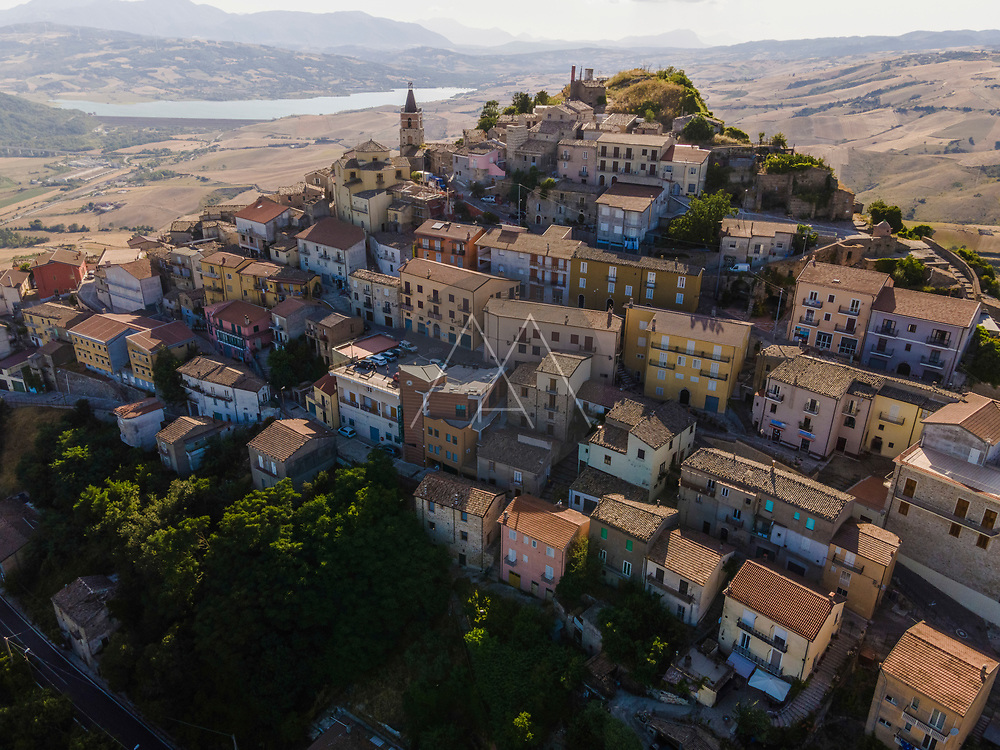 Aerial view of Cairano township on hilltop with Conza lake in background at sunset, Cairano, Irpinia, Italy.