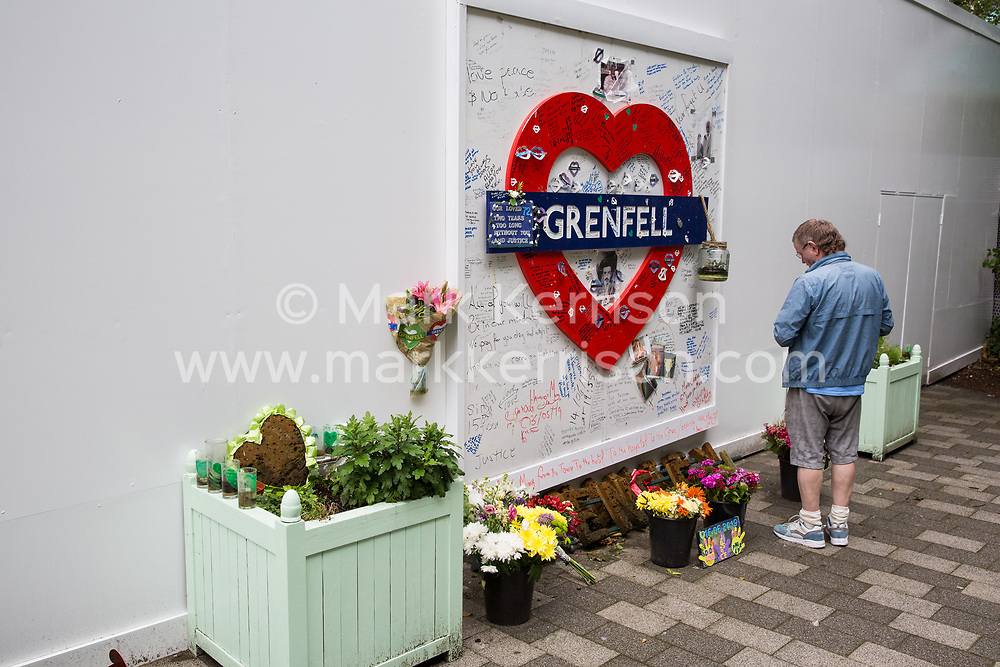 London, UK. 13 June, 2019. A man looks at tributes beneath the Grenfell Tower in North Kensington. Tomorrow, the Grenfell community will mark the second anniversary of the Grenfell Tower fire on 14th June 2017 in which 72 people died and over 70 were injured. Two years on, some family members remain in temporary accommodation and many are still traumatised. Phase 2 of the Grenfell Inquiry will begin in 2020, with criminal investigation findings expected to be sent to the Crown Prosecution Service in 2021.