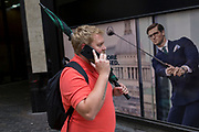 a Londoner carrying a brolly walks past a closed shop poster featuring a businessman wearing a blue suit - a favoured style and colour of menswear in the City of London, the capital's financial district - aka the Square Mile, on 29th August 2018, in London, England.