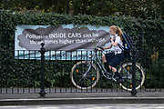A schoolgirl cyclist passes a pollution awareness banner that is attached to the railings of Dulwich Hamlet School, where restrictions also prevent traffic from passing through at morning and afternoon rush-hour times in the borough of Southwark, on 14th June 2021, in London, England.