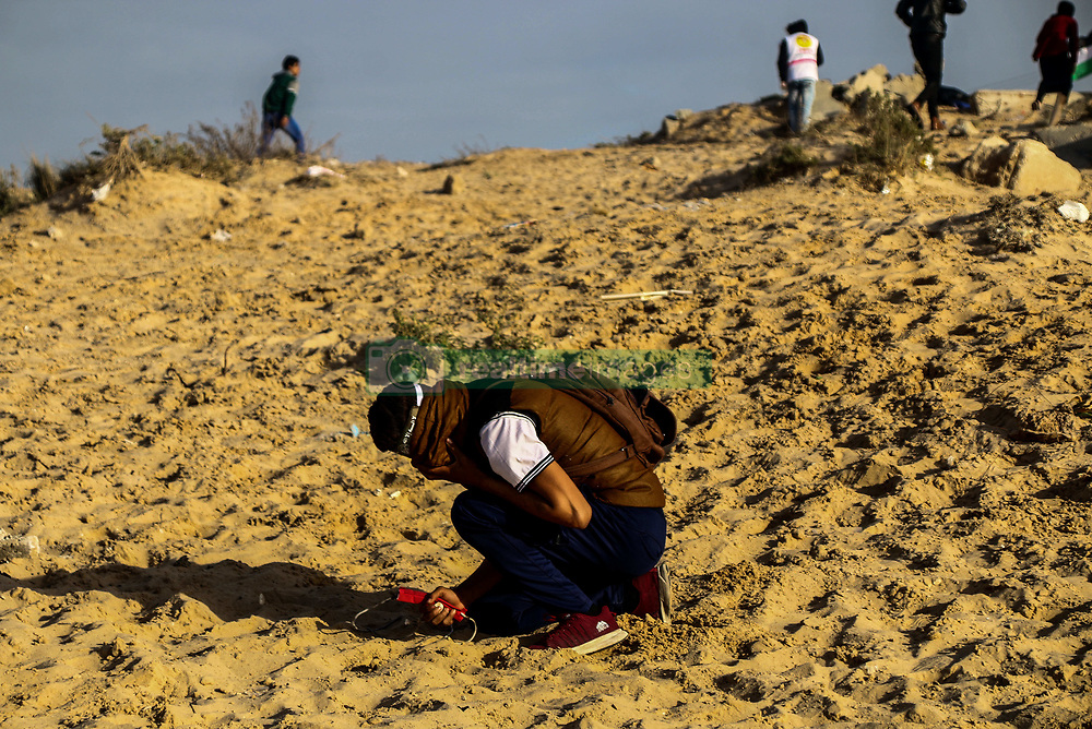 December 17, 2018 - A number of Gaza demonstrators are injured during clashes with Israeli Security Forces on the coast near Beit Lahia, in northern Gaza, on 17th December 2018, during the 20th weekly naval rally. Palestinian protesters threw stones using slingshots while Israeli troops used rubber and live ammunitions and fired teargas canisters to disperse the protesters injuring at least 20 of them with gunshots and tear gas inhalation. Red Crescent paramedic, Ahmad Abdel Bari Al-Ful, was injured in his left arm by a rubber bullet fired by Israeli troops while he was on duties during the protest. A freedom flotilla made up of several boats flying Palestinian flags also attempted to break Israel's naval siege northwest of the city of Beit Lahia, and it was also met by Israeli fire from Israeli war boats. Palestinians in Gaza have held weekly protests for several months to challenge the Israeli siege on the coastal enclave as well as the Israeli naval blockade which limits the nautical miles for fishing to Palestinians in the waters off the Gaza shores. The blockade on Gaza has caused a serious decline in the standard of living of the impoverished enclave driving the economy on the brink of collapse and bringing Gaza close to a humanitarian catastrophe (Credit Image: © Ahmad Hasaballah/IMAGESLIVE via ZUMA Wire)