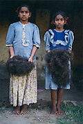 In the town of Eleru in the state of Andhra Pradesh two young sisters hold village hair they have untangled. Village hair often arrives full of dirt and knots, because of their small and nimble fingers children often get the labourious and difficult job of sorting this hair.