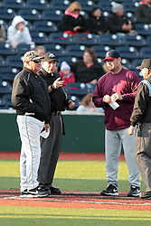 16 May 2014:  Umpires  David Fields (Plate), Dennis George (field) and managers Brooks Carey and Andy McCauley meet to exchange lineups during a Frontier League Baseball game between the Evansville Otters and the Normal CornBelters at Corn Crib Stadium on the campus of Heartland Community College in Normal Illinois
