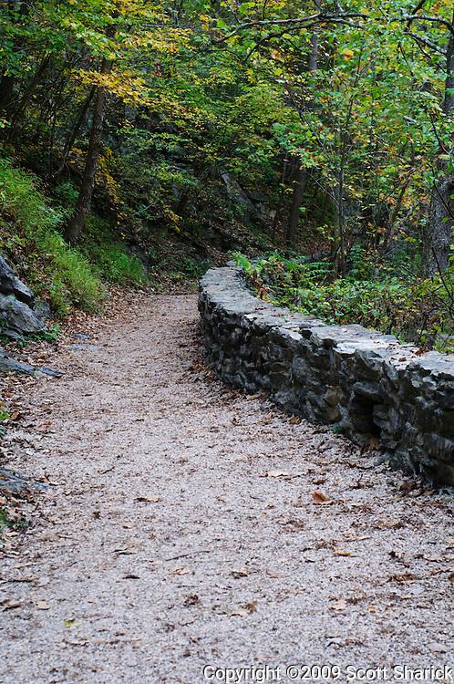 A dirt path with a rock wall follows Cedar Creek in Natural Bridge in Virginia.